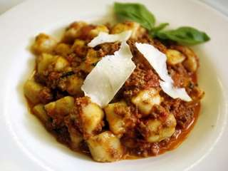 Homemade ricotta gnocchi with Bolognese is served at