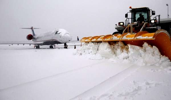Plows clear snow near a plane at MacArthur