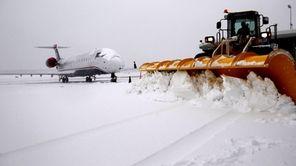 Plows clear snow near a plane at MacArthur