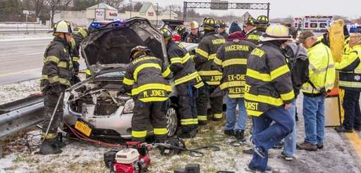 Firefighters work to remove a woman trapped in