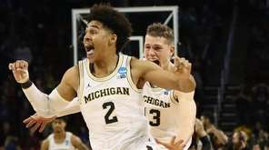 Jordan Poole and Moritz Wagner of the Michigan