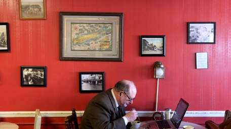 A patron eats while working on his laptop