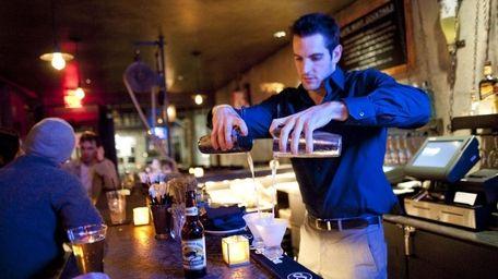 Bartender Harrison Platz mixes drinks behind the bar