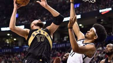 Raptors center Jonas Valanciunas shoots over Nets center