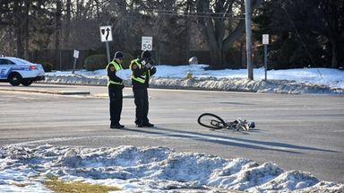Police investigate the scene where a bicyclist was