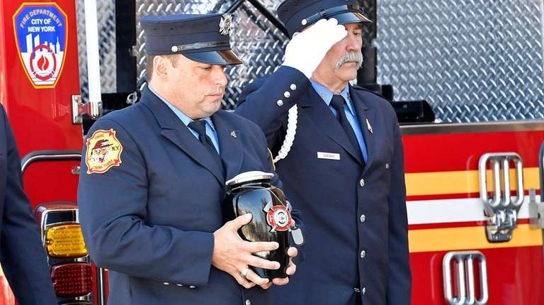 An FDNY firefighter carries the urn containing the