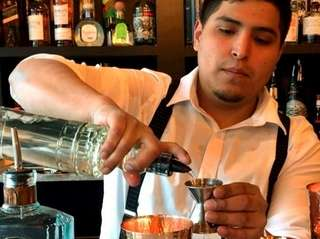 Barndoor 49 bar manager Anthony Lucero measures out