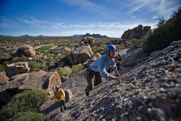 People rock climb at the Boulders Resort in