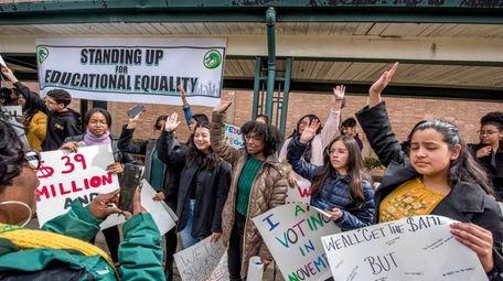 Students at Westbury High School raise their hands