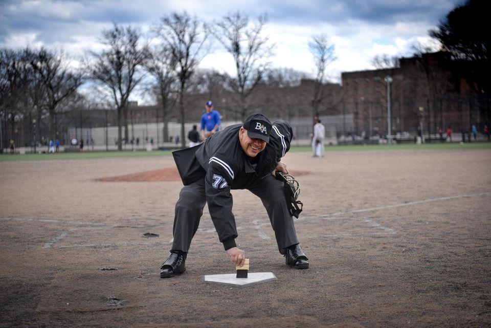 Big Apple Umpire School student Geoffrey Hernandez brushes