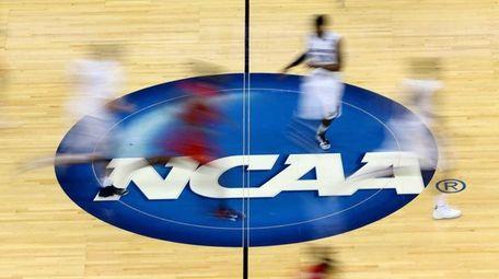 The NCAA logo on a basketball court.