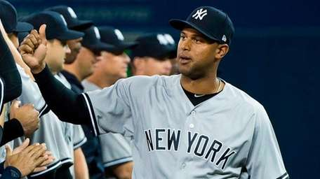 Yankees centerfielder Aaron Hicks, right, high-fives teammates as