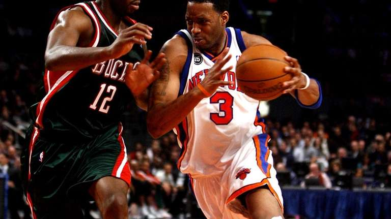 Knicks' Tracy McGrady drives past Milwaukee Bucks Luc