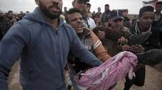 Palestinian protesters carry a wounded man who was