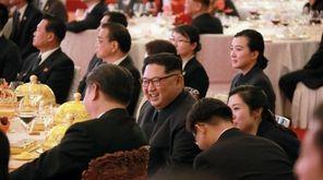 North Korean leader Kim Jong Un, center, smiles