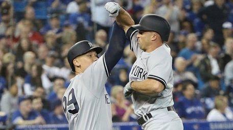 Yankees outfielder Brett Gardner is congratulated by Aaron