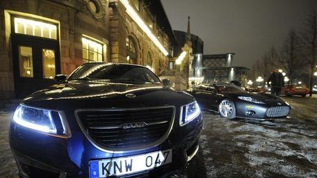 A saab car (L) exposed near a Spyker