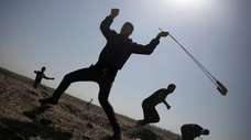 A Palestinian protester hurls stones at Israeli soldiers