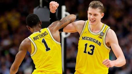 Michigan's Moritz Wagner celebrates with Charles Matthews during