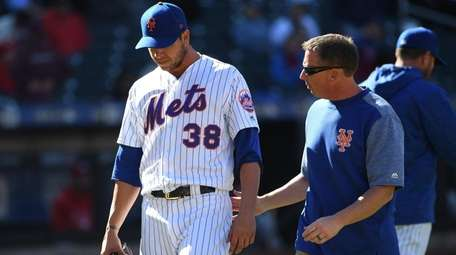 A Mets trainer escorts Mets relief pitcher Anthony