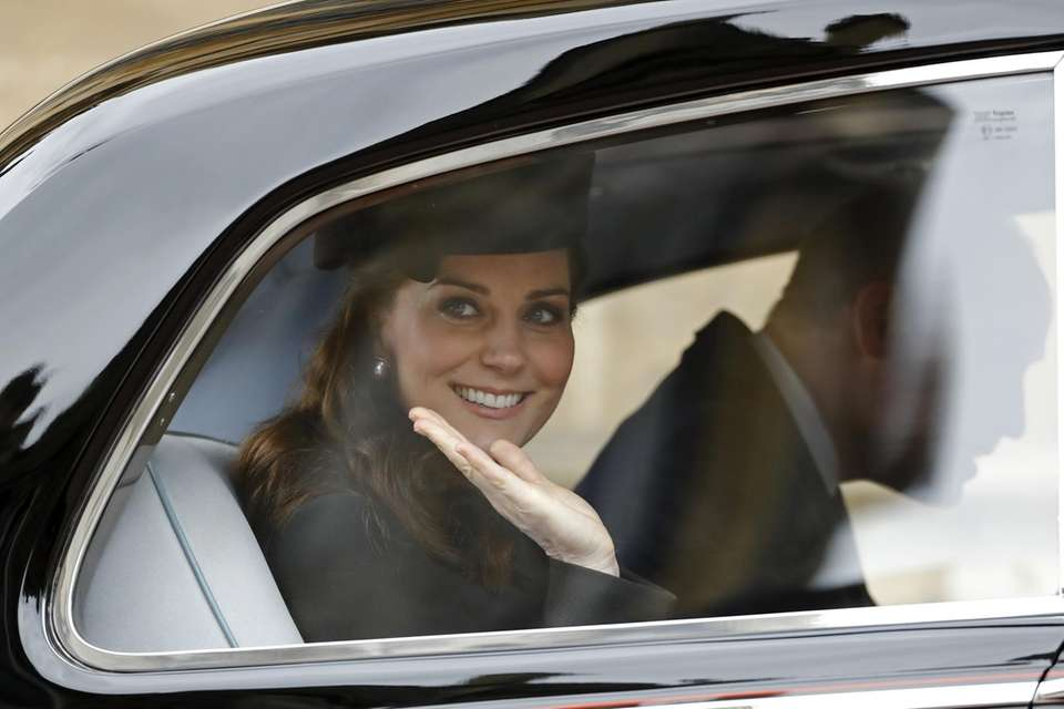 Catherine, Duchess of Cambridge waves from her car