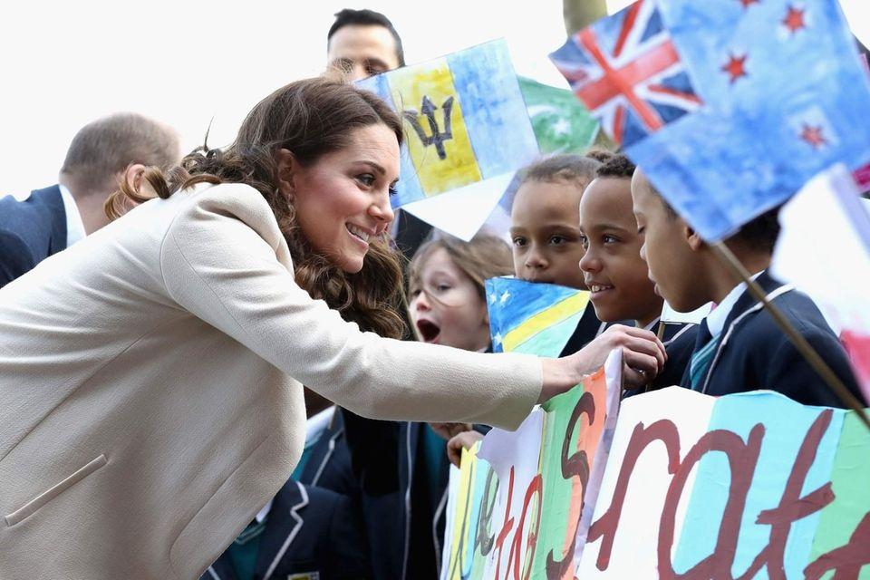 Catherine, Duchess of Cambridge greets children on her