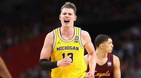 Moritz Wagner #13 of the Michigan Wolverines celebrates