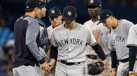 Yankees starting pitcher Sonny Gray, center, is taken