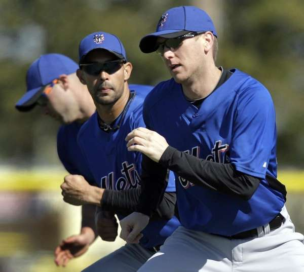 New York Mets' Jason Bay, right, works on