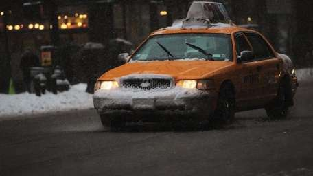 A taxi moves on a slushy Sixth Avenue