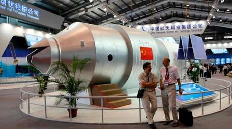 Visitors sit beside a model of China's Tiangong-1