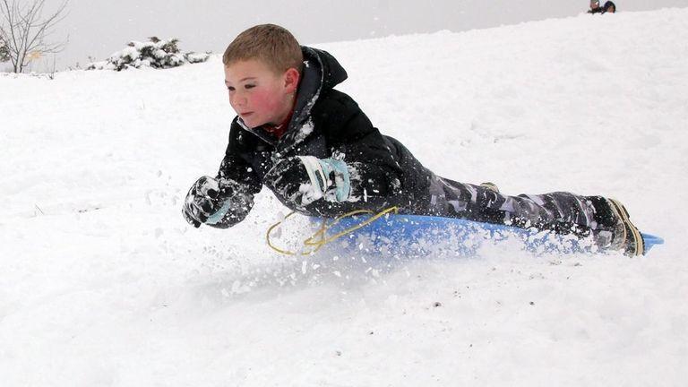 Spencer Schwarz, 7, slides down a hill in