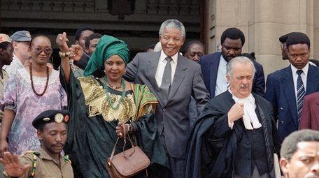 Winnie Mandela, and husband, Nelson Mandela, walk out