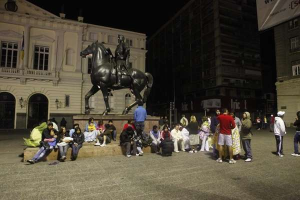Residents sit in a main square in downtown