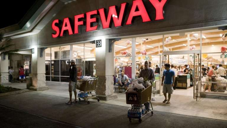 Shoppers leave a grocery store with their purchases