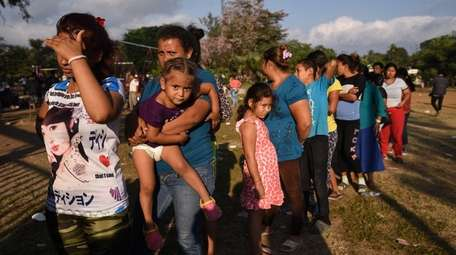 Central American migrants line up for food in