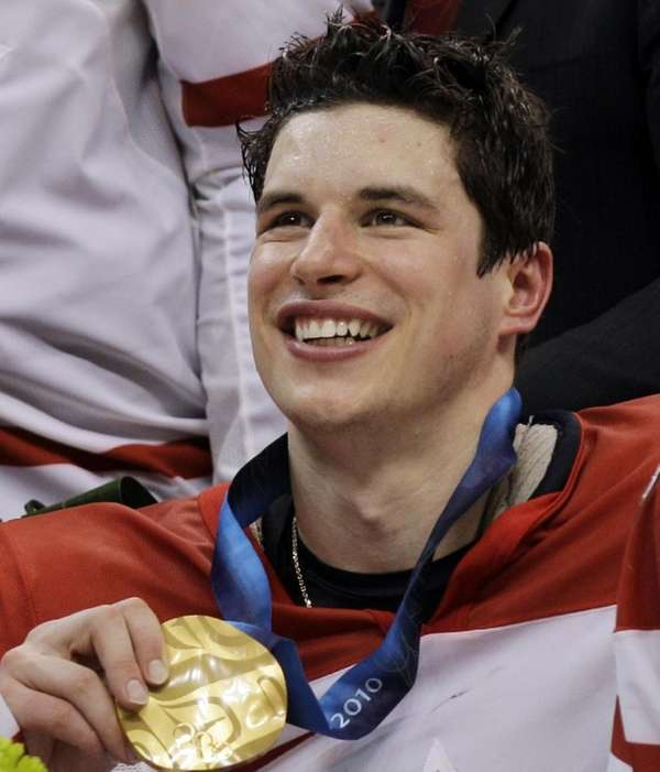Canada's Sidney Crosby (87) holds his gold medal