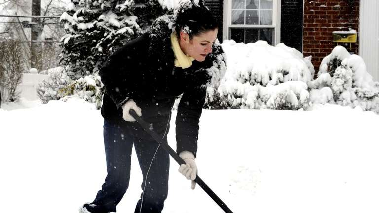 Amy Fischer shovels snow in front of her
