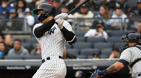 Yankees leftfielder Giancarlo Stanton follows through on a