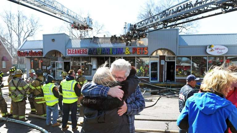 Pet shop owner Joe Carpinone, facing, is comforted
