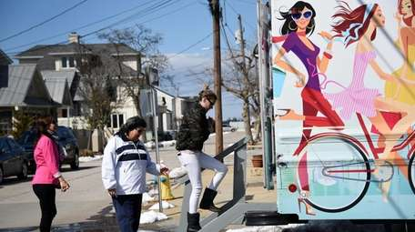 Customers enter Lola's Lookbook, a mobile boutique, parked