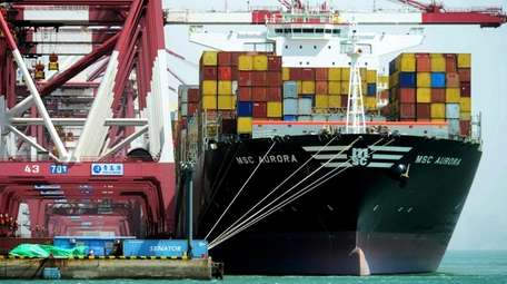 Containers are loaded onto a cargo ship at