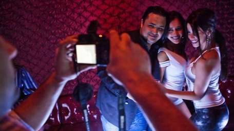 A man takes a picture of two woman