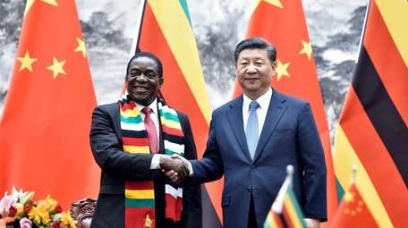 Zimbabwean President Emmerson Mnangagwa, left, shakes hands with