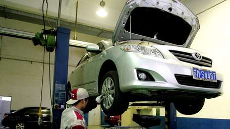 A mechanic checks a vehicle at a Toyota