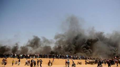 Palestinian protesters gather on a hill as others