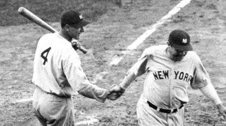 Babe Ruth is greeted at home plate by