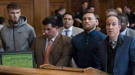 Conor McGregor, foreground second right, is arraigned in