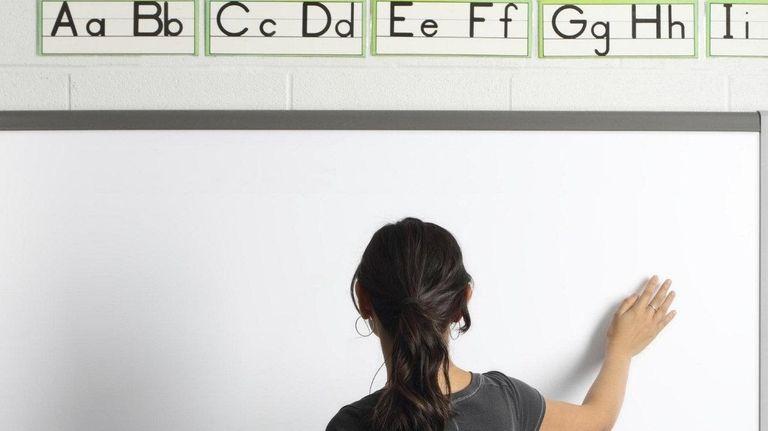 A teacher at a smartboard.