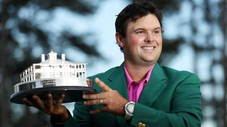 Patrick Reed celebrates with the trophy during the